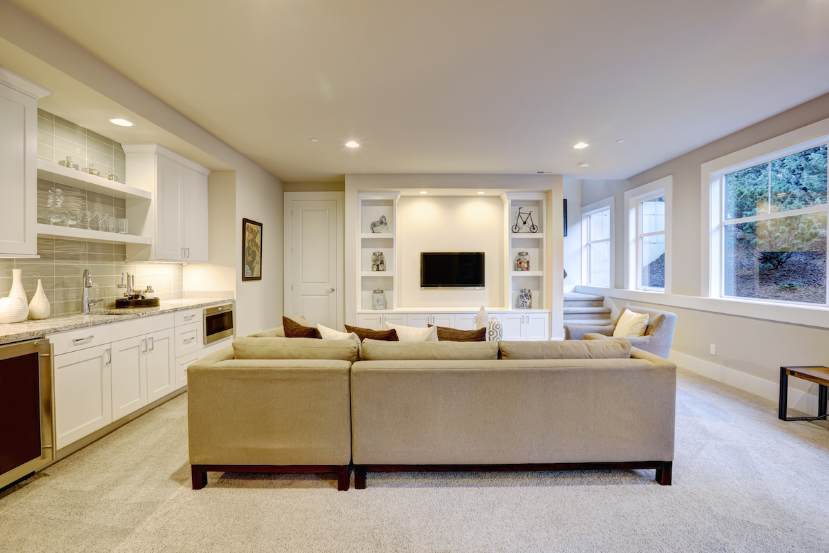 basement with beige carpet, built in bar with granite countertops and a built in entertainment center